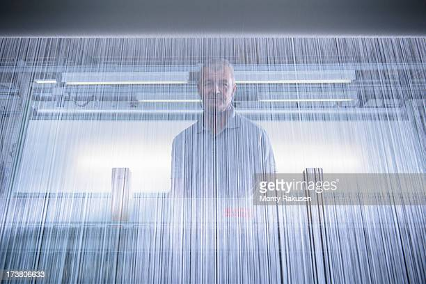 Portrait of worker operating industrial loom in textile mill