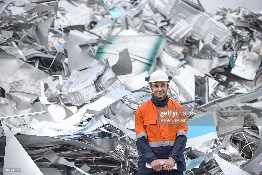 Portrait of worker standing in front of scrap in aluminium recycling plant