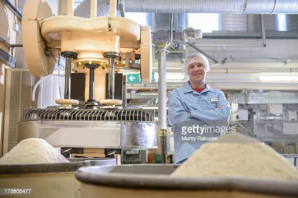 Portrait of worker standing next to mixing machine in biscuit factory