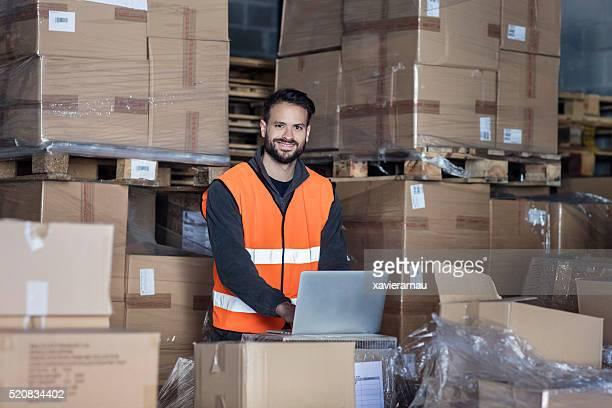 Portrait of worker using laptop in warehouse