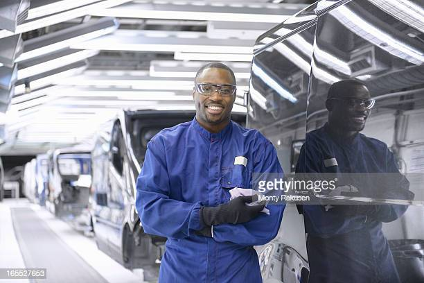 Portrait of worker wearing boiler suit and protective goggles in car factory