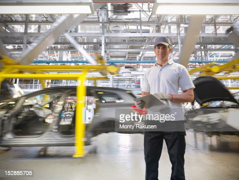 Portrait of worker with cars on production line in car factory