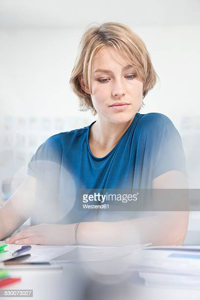Portrait of working young woman at her desk in a creative office