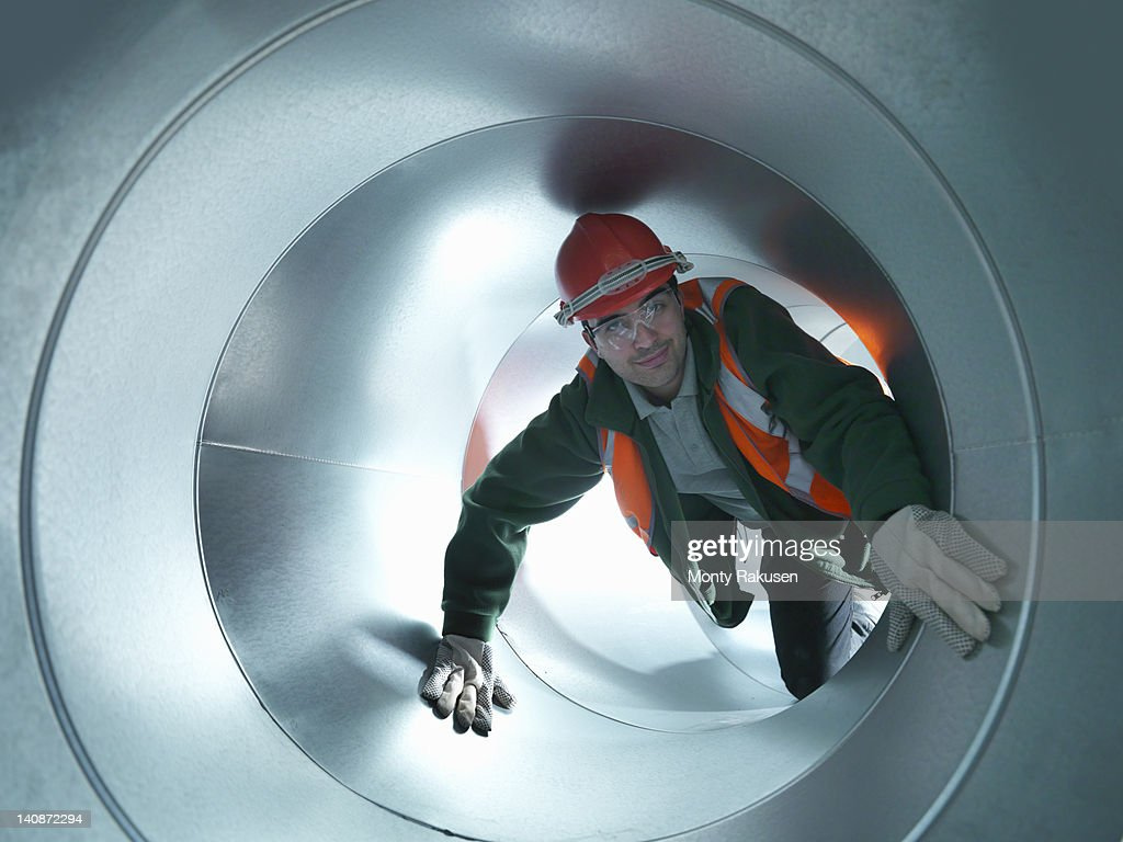 Portrait of workman in stainless steel air pipe of building site
