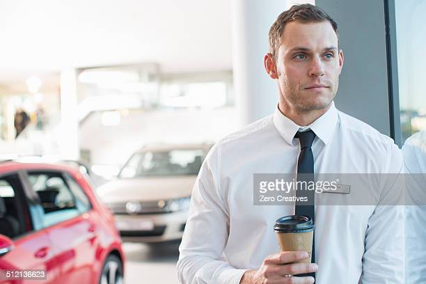 Portrait of worried salesman with takeaway coffee in car dealership