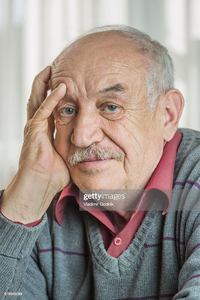 Portrait of worried senior man with hand on face at home