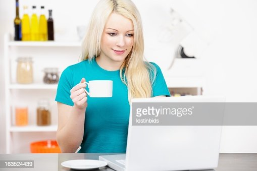 Portrait Of Young Adult Female Using  Laptop In The Kitchen : Stock Photo