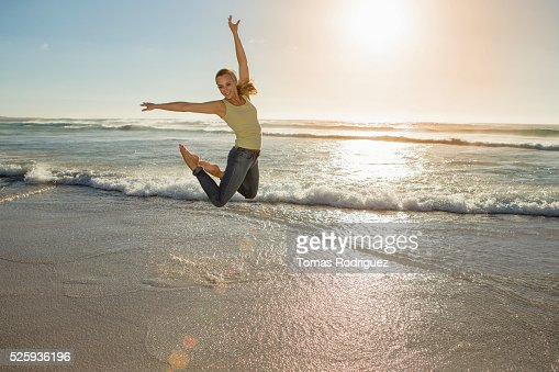 Portrait of,, young adult woman jumping on beach : Foto de stock