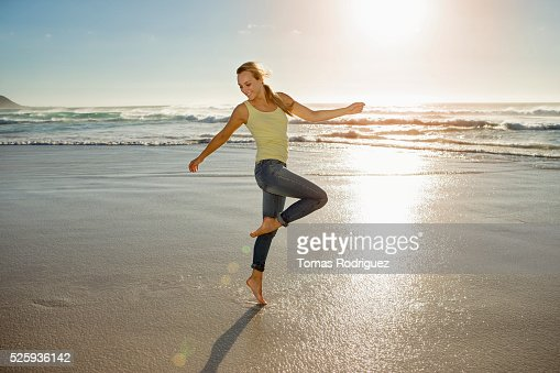 Portrait of young adult woman on beach standing on one leg : Stockfoto
