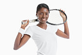 Portrait of young African American woman holding racket over white background