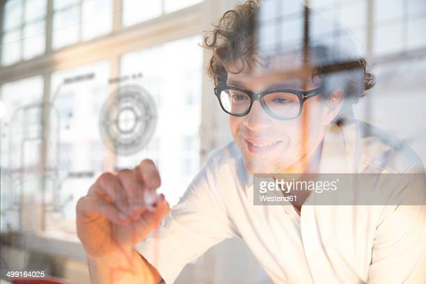 Portrait of young architect fastening construction plan on glass pane in office
