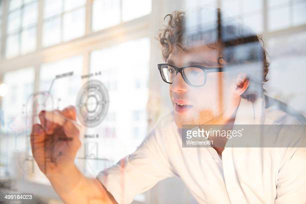 Portrait of young architect marking construction plan in office