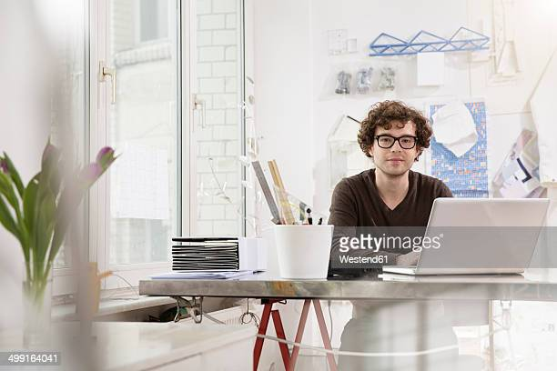 Portrait of young architect sitting at desktop in his office
