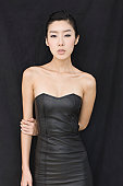 Portrait of young Asian woman in leather dress.