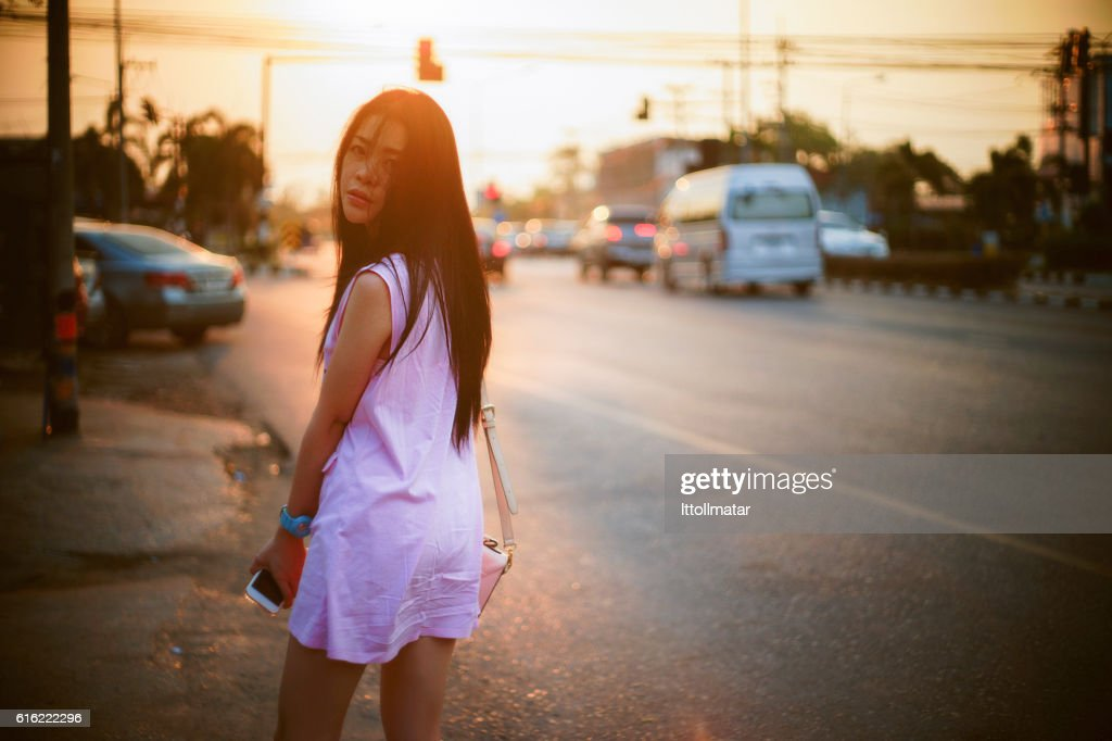 Portrait of young asian woman standing at sunset moment : Stock Photo