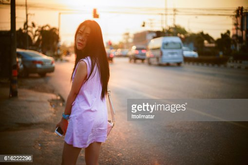 Portrait of young asian woman standing at sunset moment : Stockfoto
