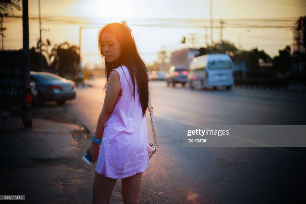Portrait of young asian woman standing side of street : Stock Photo