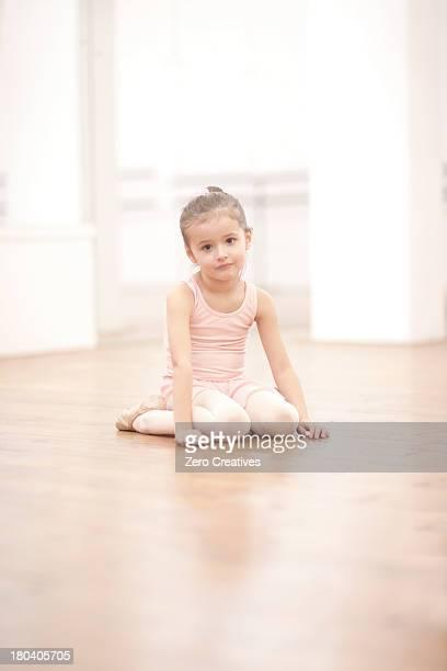 Portrait of young ballerina sitting on floor