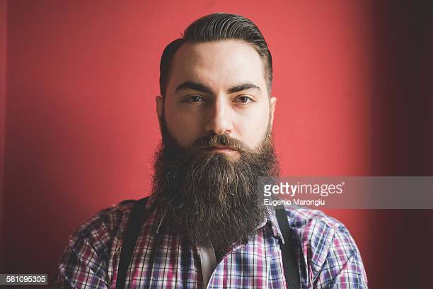 Portrait of young bearded man, red background