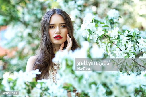 Portrait of young beautiful woman in spring blossom trees. : Stock Photo