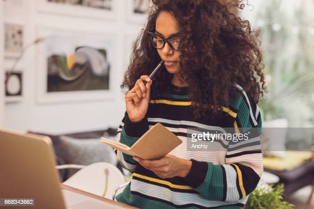 portrait of young beautiful woman taking notes.