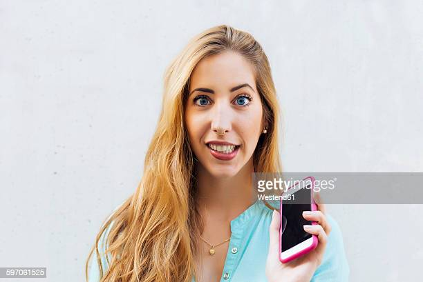 Portrait of young blond woman with smartphone
