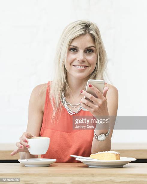 Portrait of young blonde woman holding cell phone and coffee