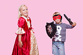 Portrait of young boy and girl in stage costume over pink background