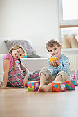 Portrait of young boy drinking orange juice while sitting with sister on floor