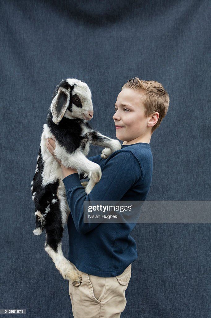 Portrait of young boy holding baby goat