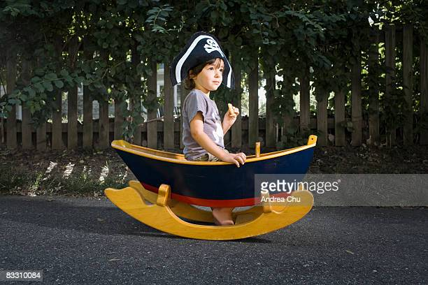 Portrait of young boy in toy boat with cookie.