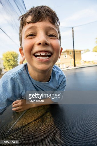 Portrait of young boy leaning on large trampoline, laughing