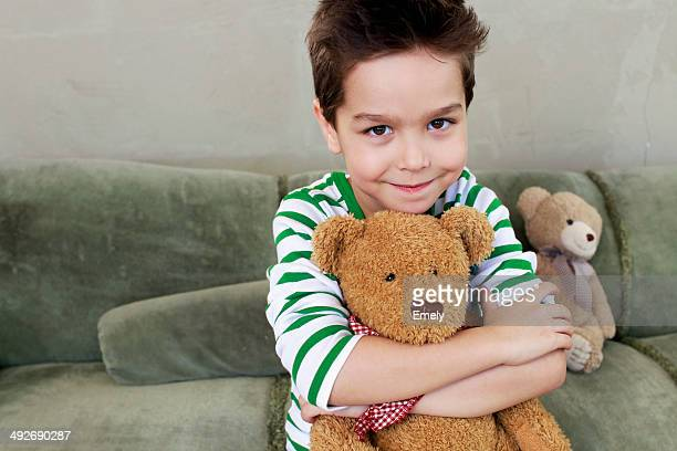 Portrait of young boy on sofa hugging teddy