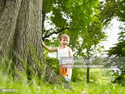 Portrait of young boy playing in grassy park : Stock Photo