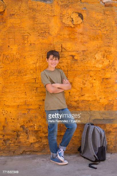 Portrait Of Young Boy Standing Against Yellow Wall