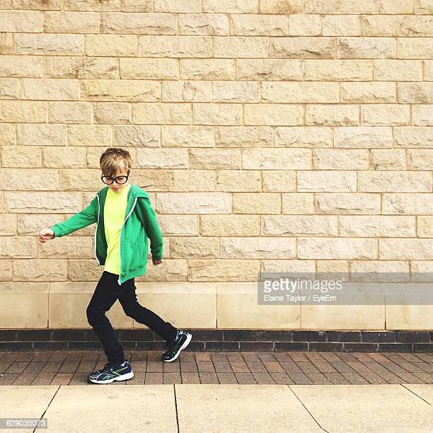 Portrait Of Young Boy Standing On Sidewalk
