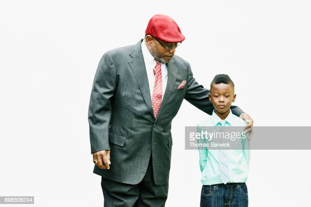 Portrait of young boy standing with uncle in front of white background
