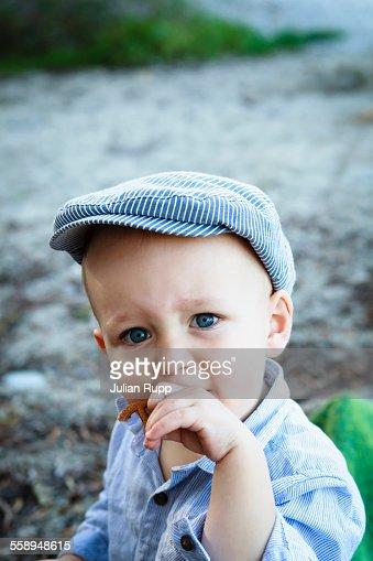 Portrait of young boy wearing flat cap, in rural setting