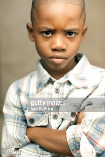 Portrait of young boy with arms crossed. : Stock Photo