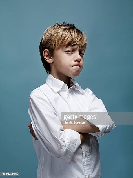Portrait of young boy with crossed arms and looks