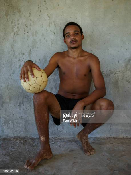 Portrait of young brazilian man holding a football