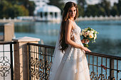 Portrait of young bride with long hairs holding her wedding bouquet includes white roses and other flowers. Beautiful white marriage dress. Pretty girl on lake background.