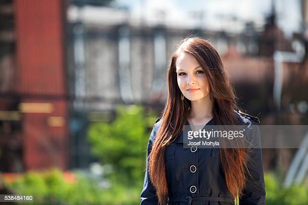 Portrait of young brunette woman in front of industry background