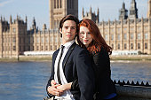 Portrait of young business couple standing together against Big Ben tower, London, UK