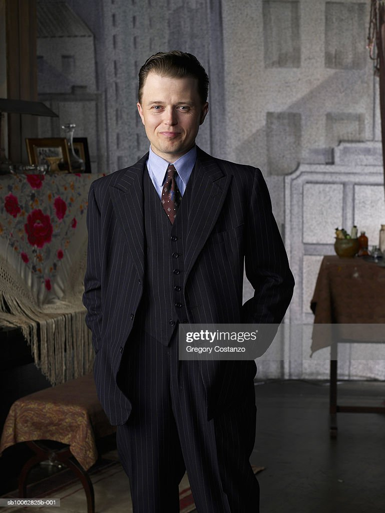 Portrait of young business man in living room, hand in pocket, smiling : Stock Photo