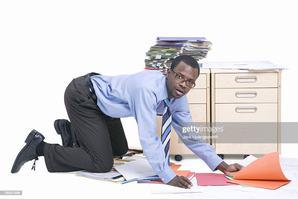 Portrait of young business man picking up folders from floor : Stock Photo