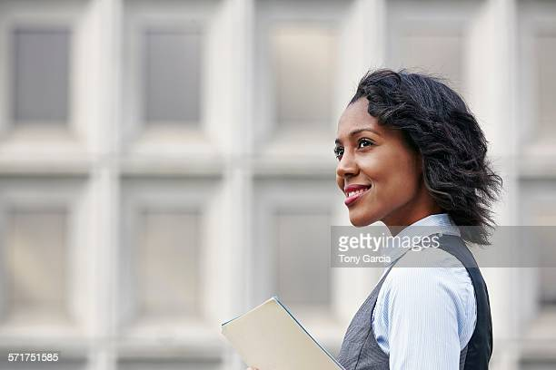 Portrait of young business woman holding paper work, looking away, smiling, side view