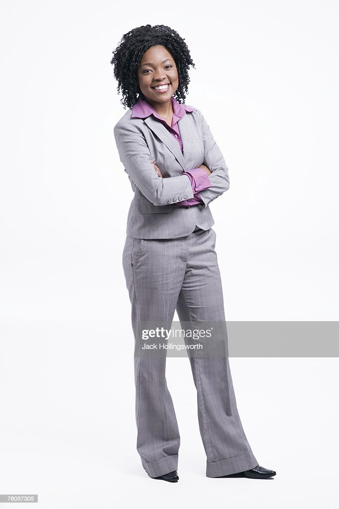 Portrait of young business woman standing with arms crossed against white background : Stock Photo