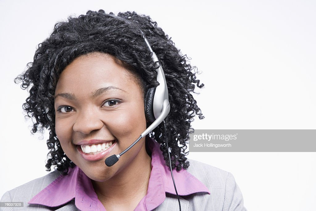 Portrait of young business woman wearing headset, smiling : Stock Photo