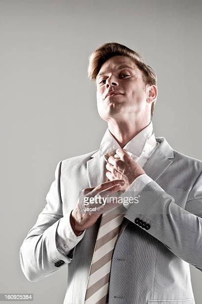 portrait of young businessman adjusting his tie